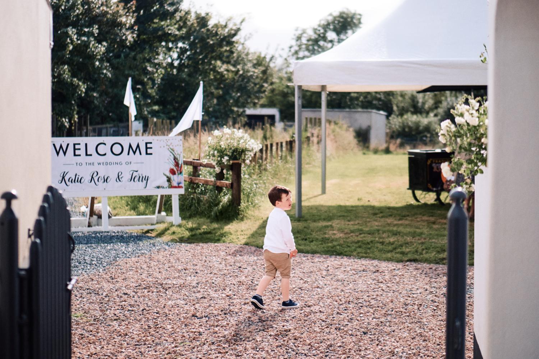 A child explores the grounds of a garden wedding reception