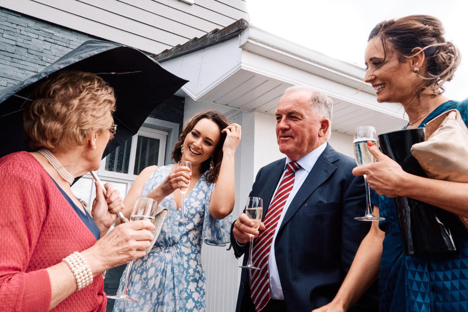 Wedding guests talk and drink champagne