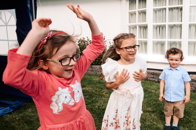 Three children dance at a wedding garden reception