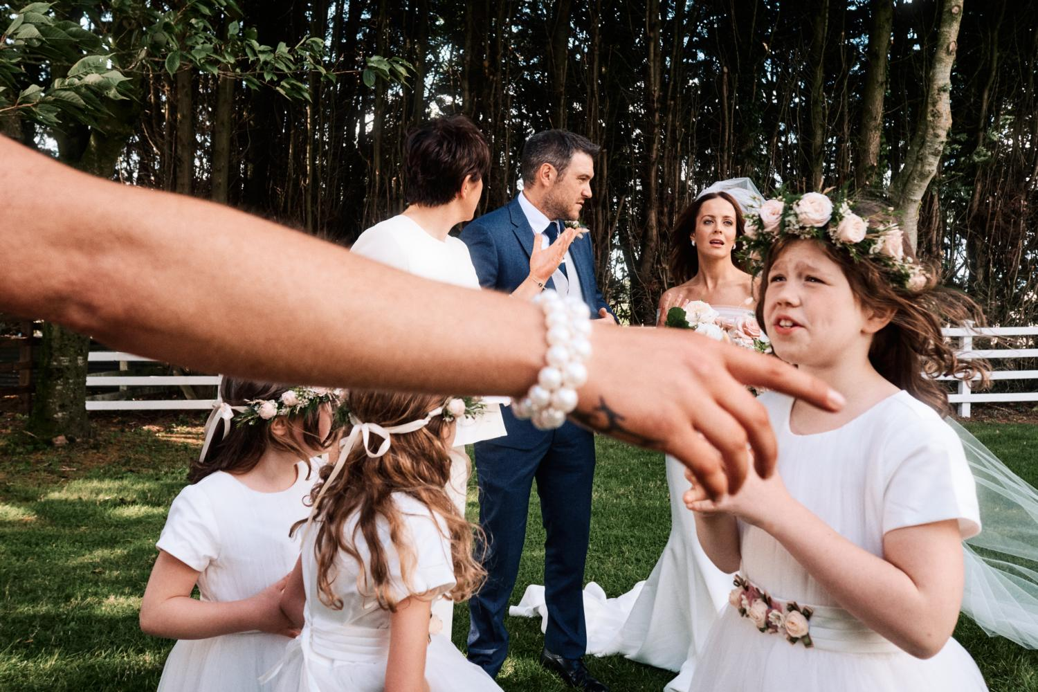 A mother points at a flower girl at a wedding