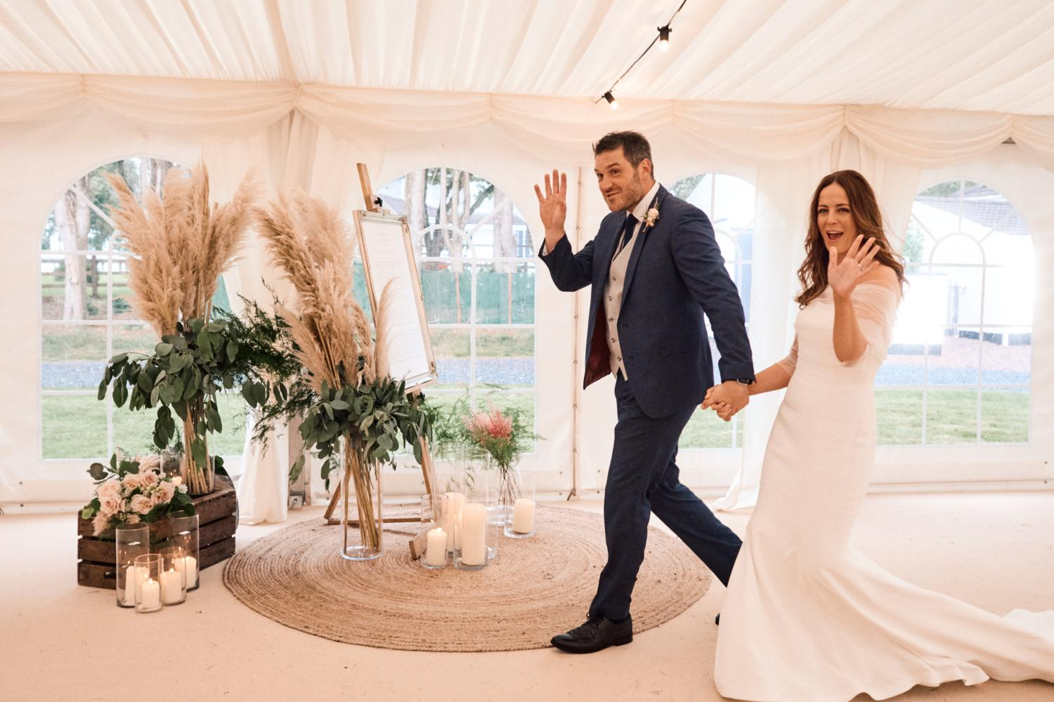 A married couple wave as they enter a marquee wedding reception
