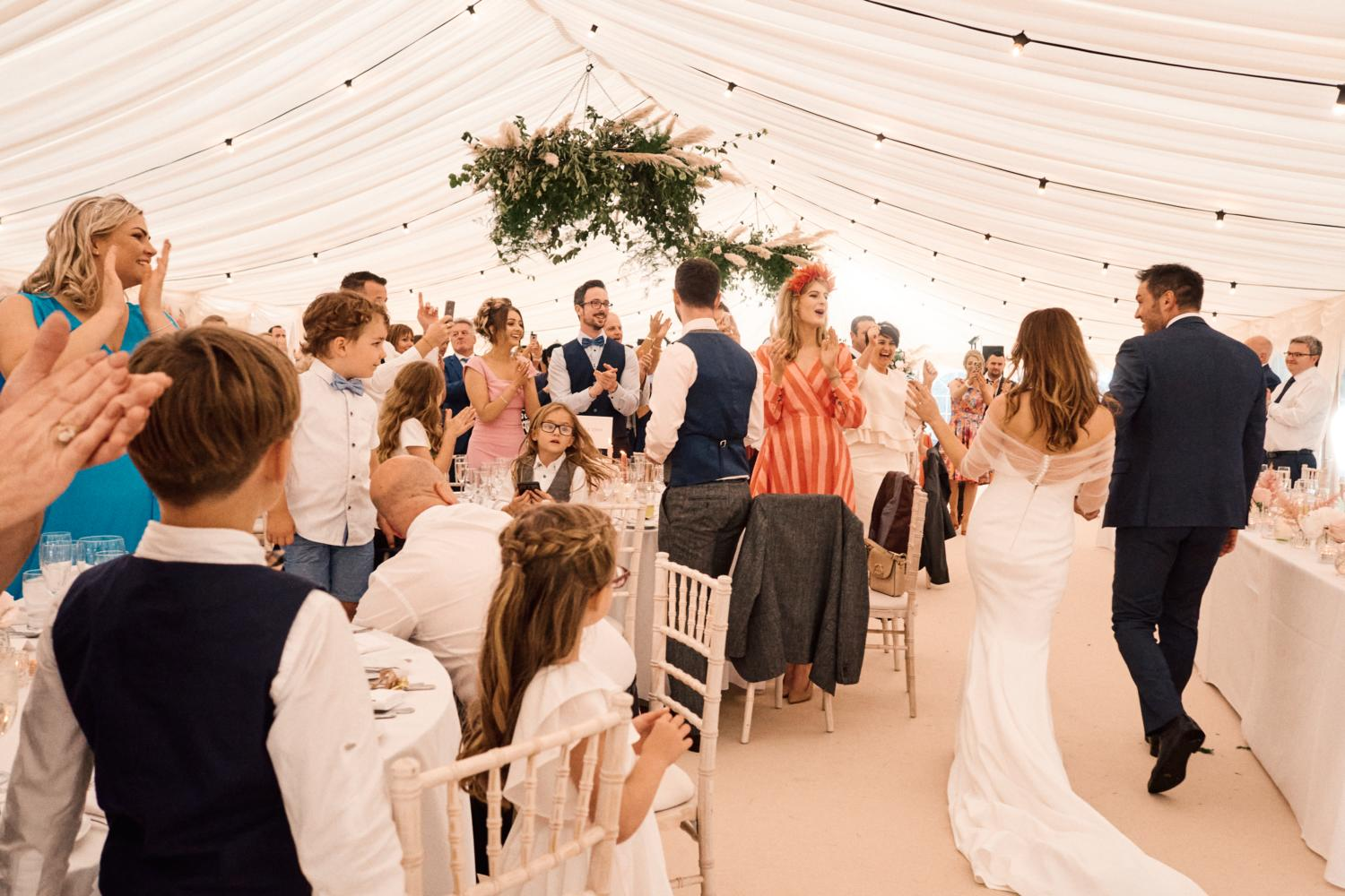 Guests celebrate the arrival of the newly wedded couple in a marquee