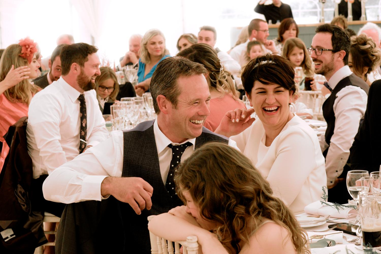 A family laugh at a table during wedding speeches in a marquee