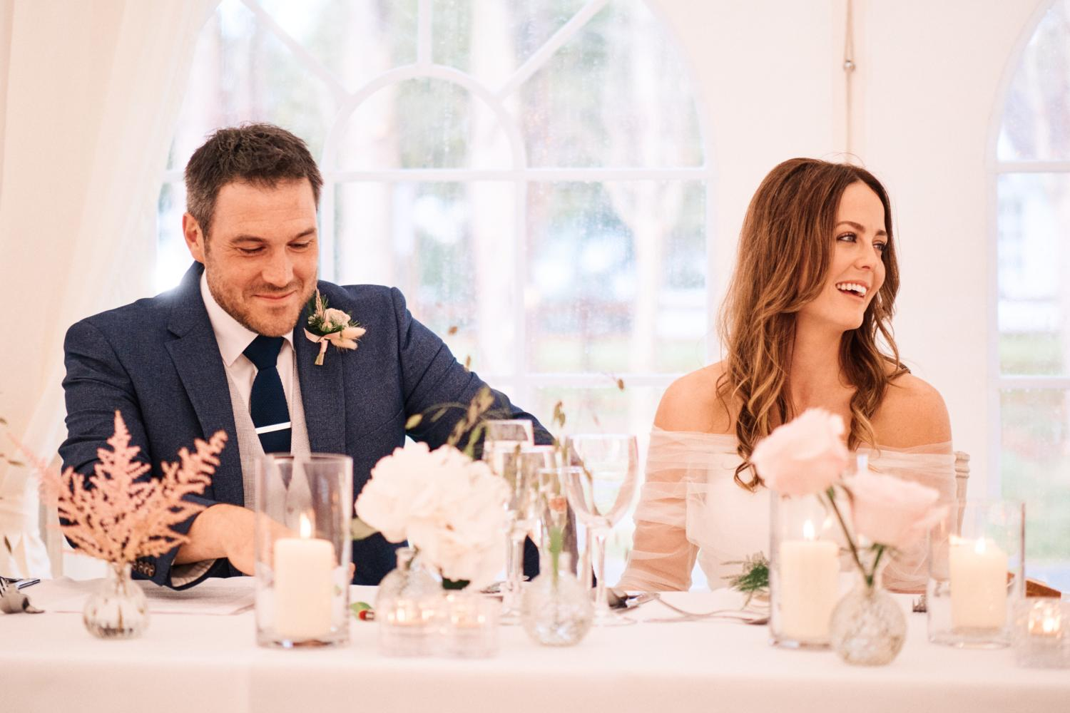 A married couple smile as they listen to the speeches