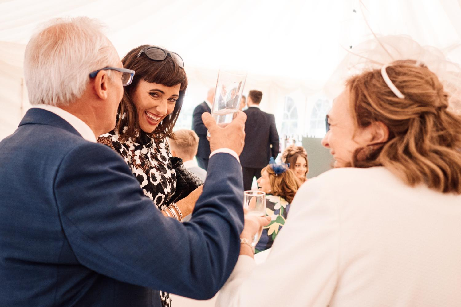 Wedding guests laugh and enjoy drinks in a marquee