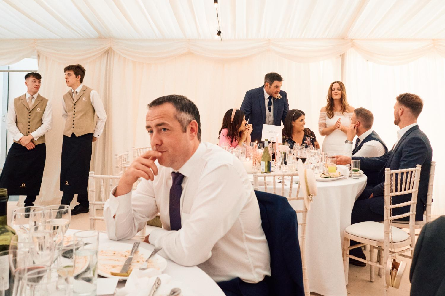 Wedding guests mingle in a marquee in the evening