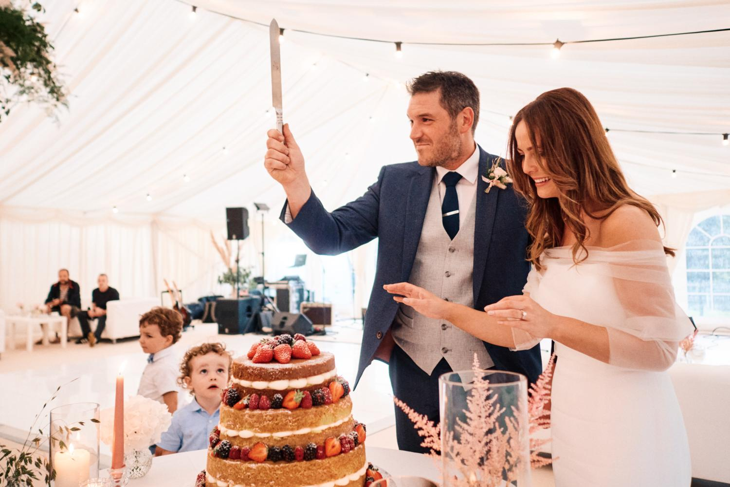 A bride and groom cut their wedding cake in front of a child