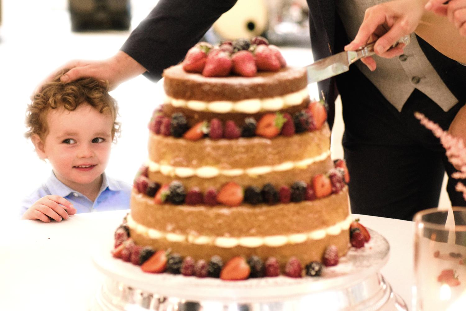 A smiling child is patted on the head by a groom in marquee in front of a wedding cake