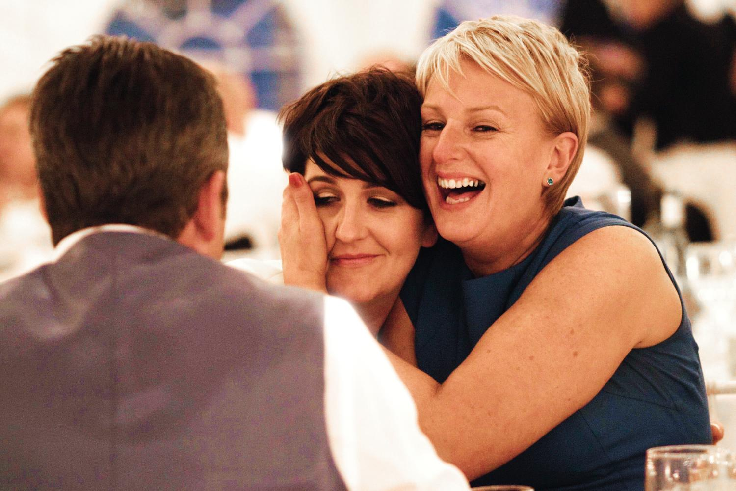 Two women hug and laugh at a wedding