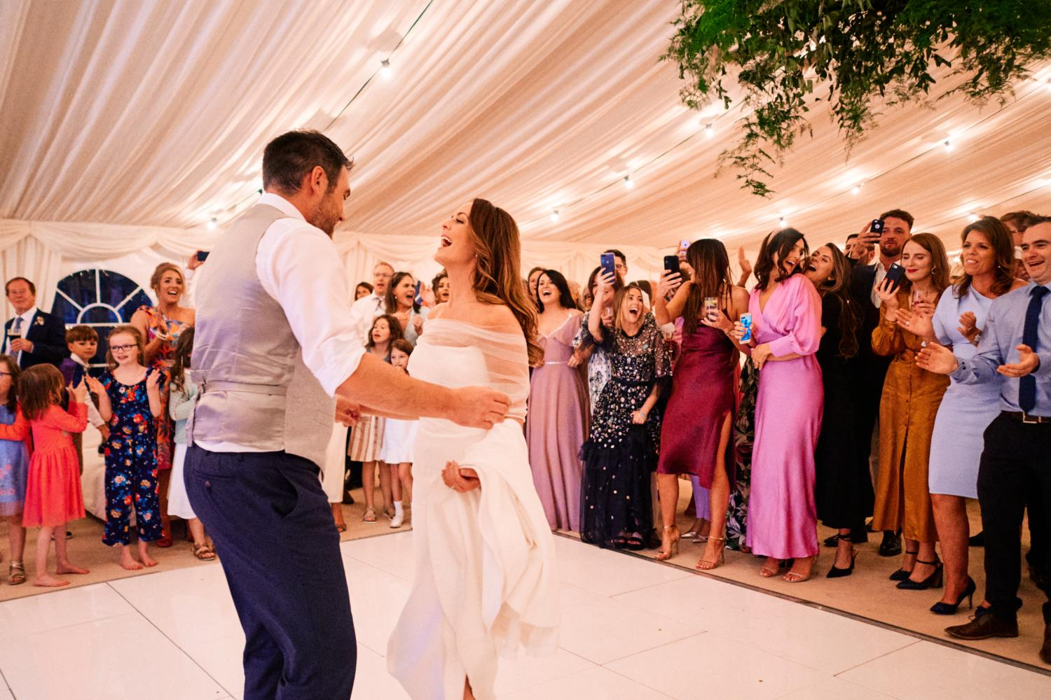 A bride and groom begin their first dance in a marquee