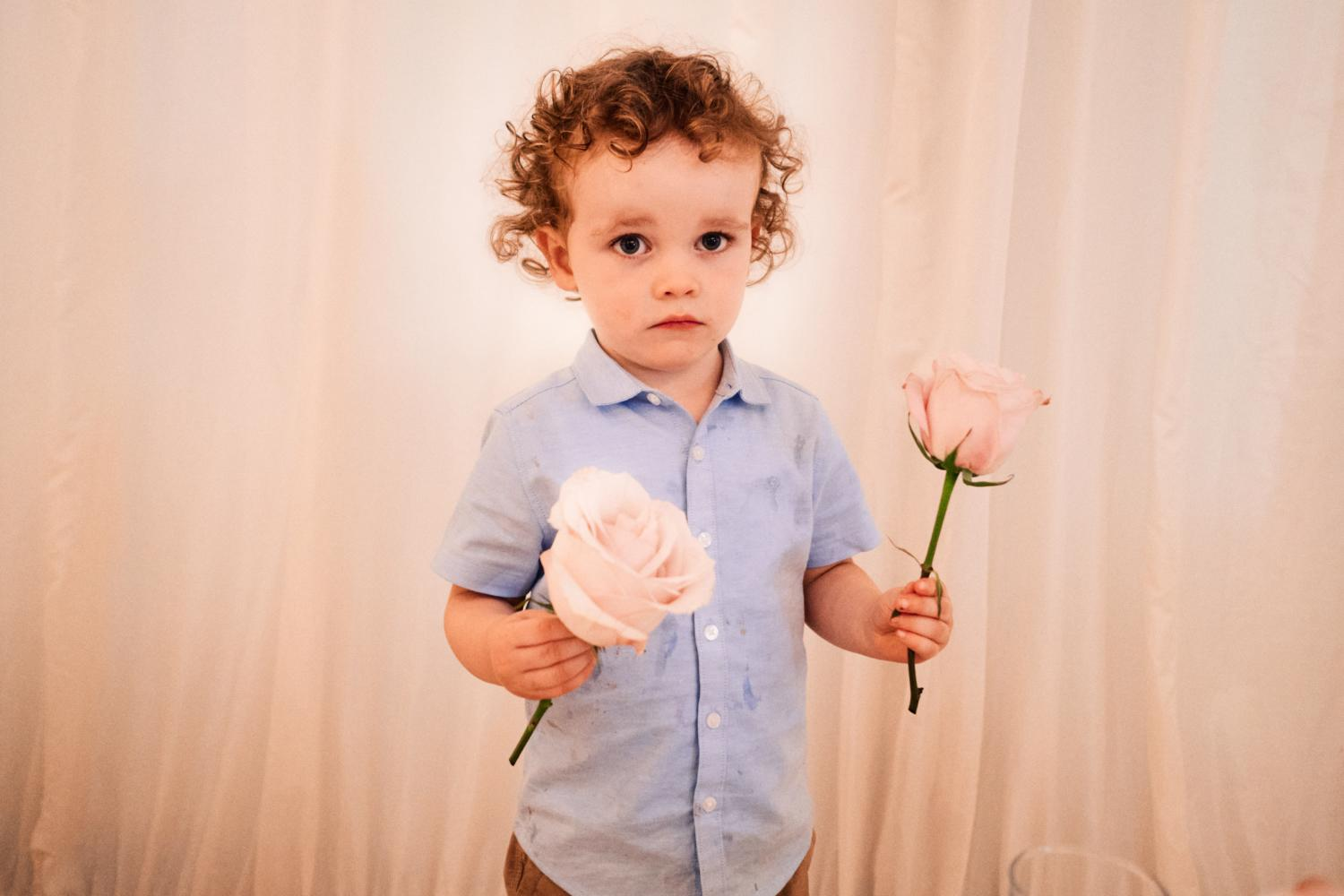 A child steals two roses at a wedding