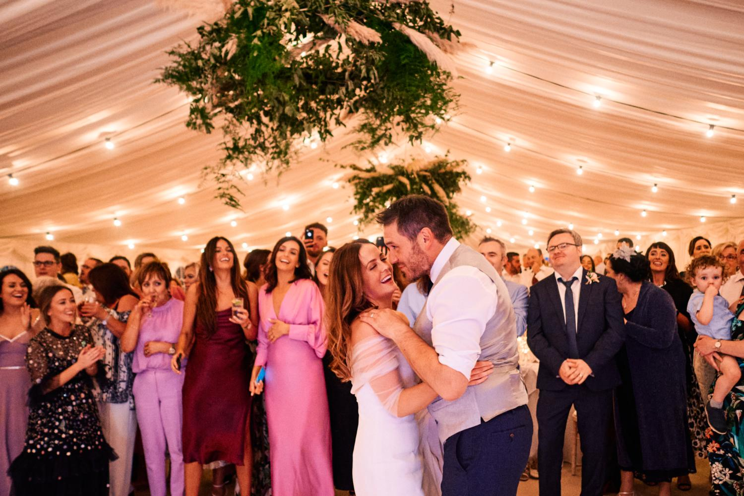 Guests watching the first dance in a marquee