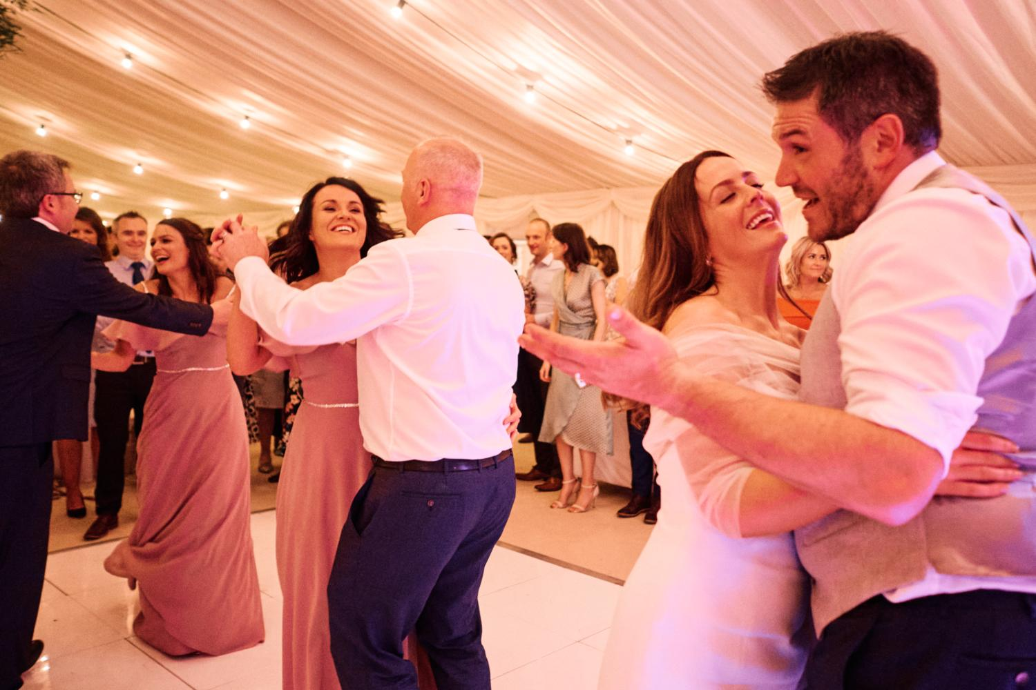 Couples dancing in a marquee at a wedding