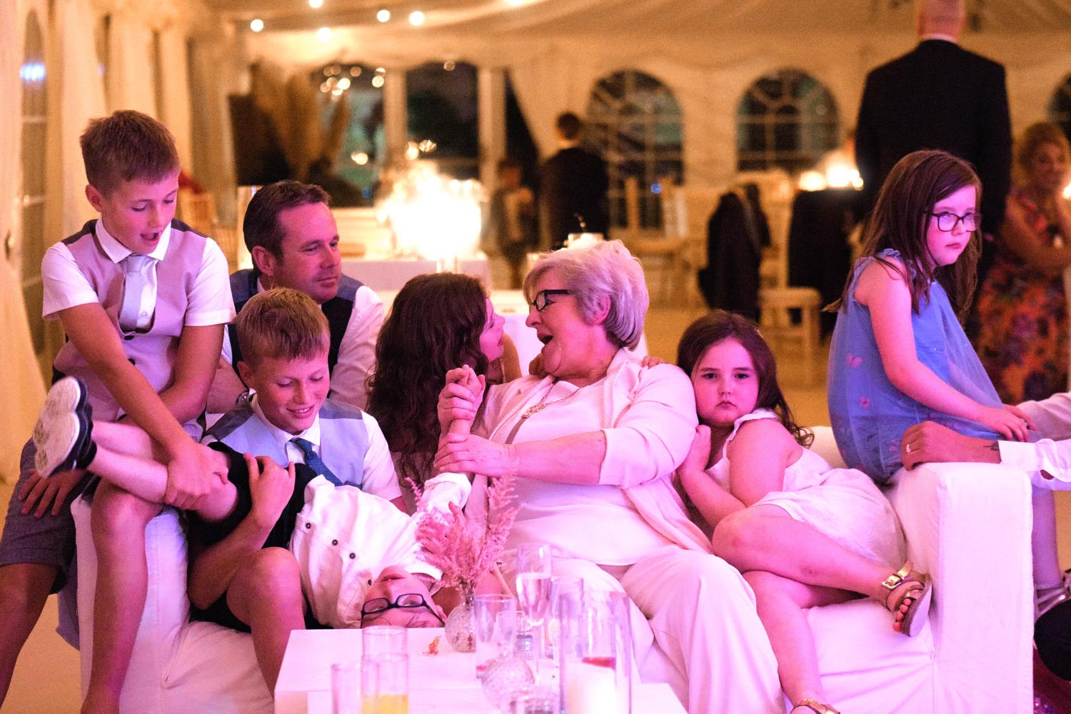 A grandmother plays with her grandchildren at a wedding