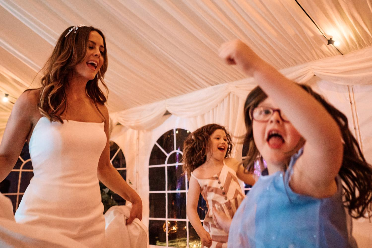 A bride dances with funny children at a wedding