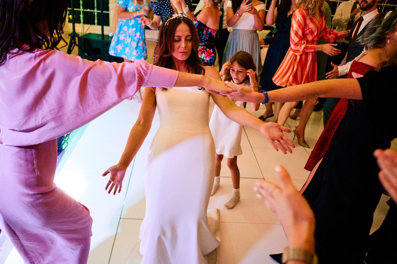 A bride plays limbo at a wedding