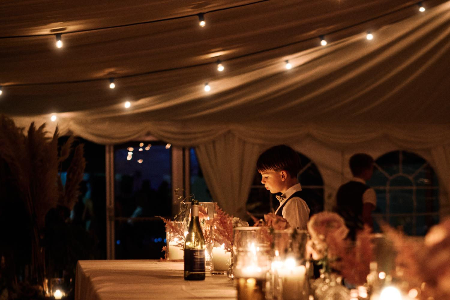 A child plays with candlelight at a marquee wedding
