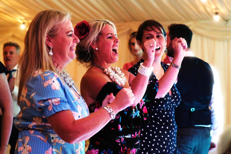 Three women singing at a wedding