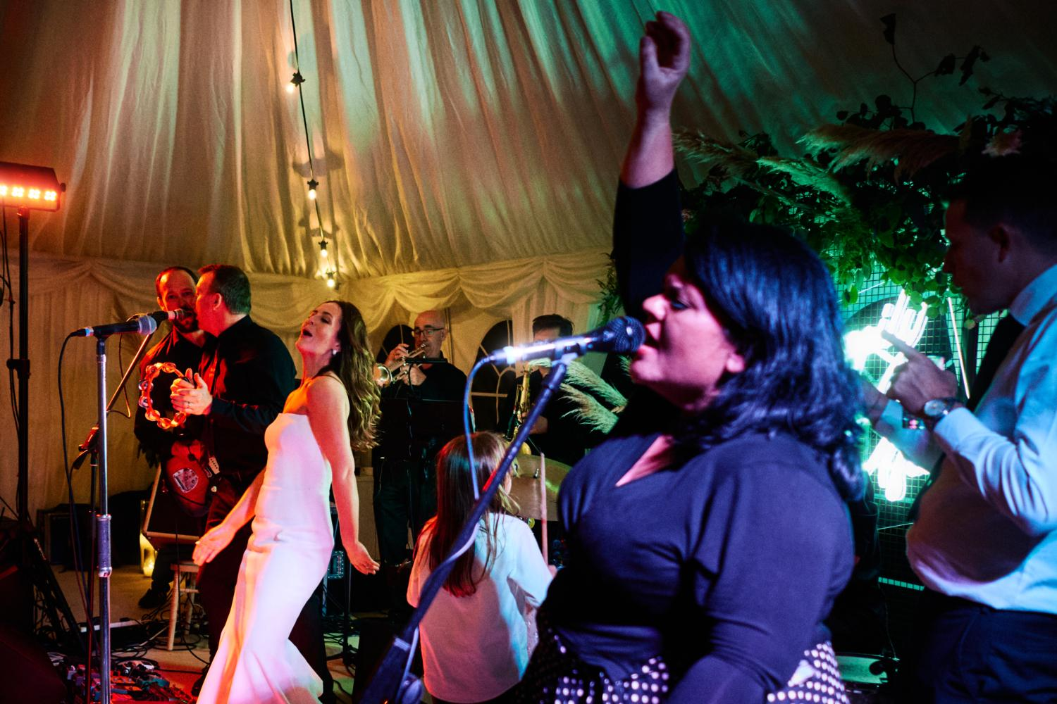 A bride sings with the wedding band in a marquee
