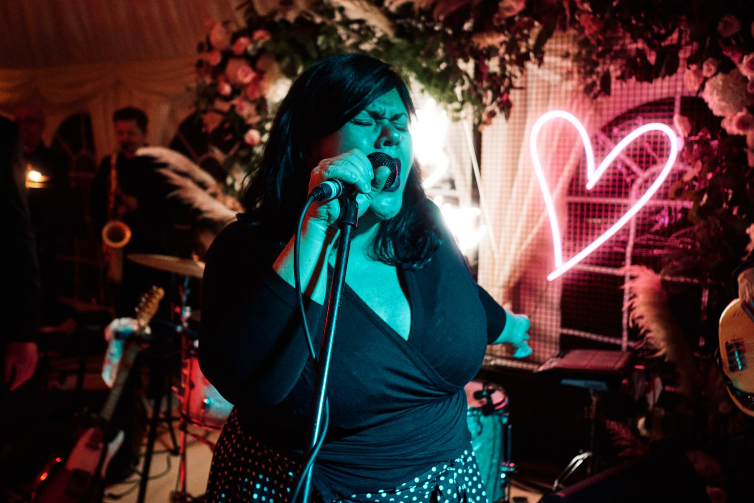 An expressive singer at a wedding, bathed in blue light