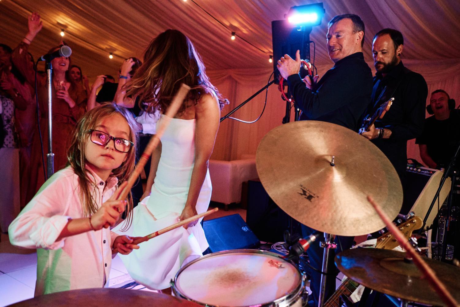 A child plays the drums at a wedding