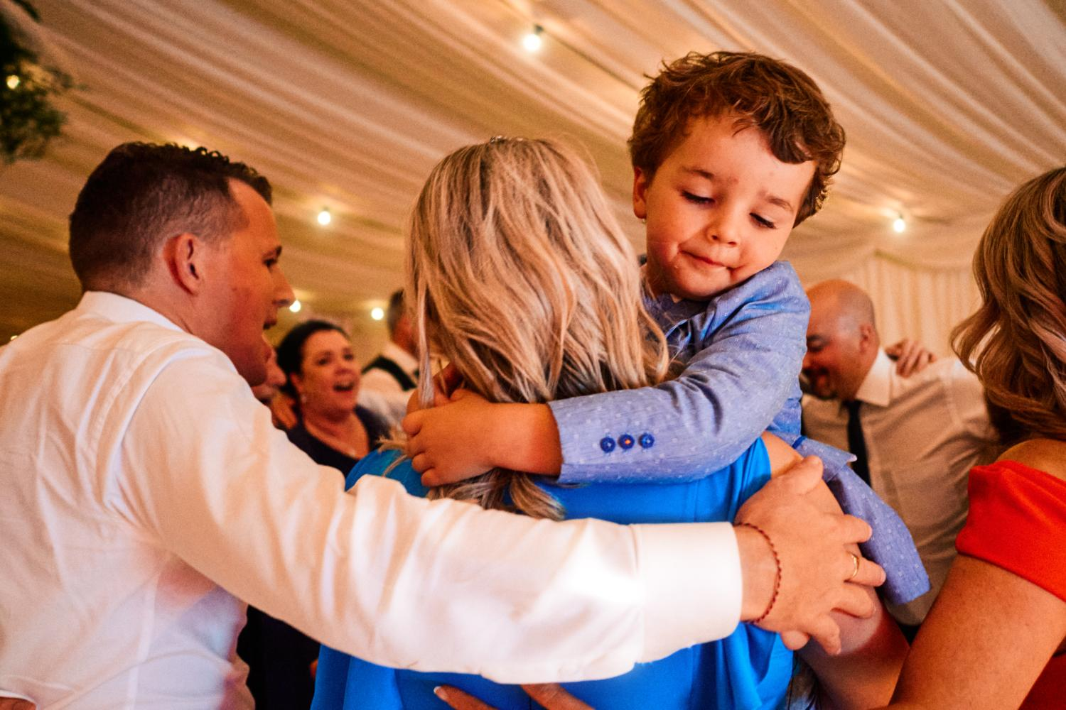 A child hugs his mother at wedding