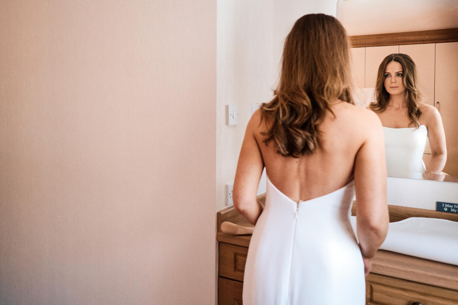 A bride in a white wedding dress, looking into the mirror