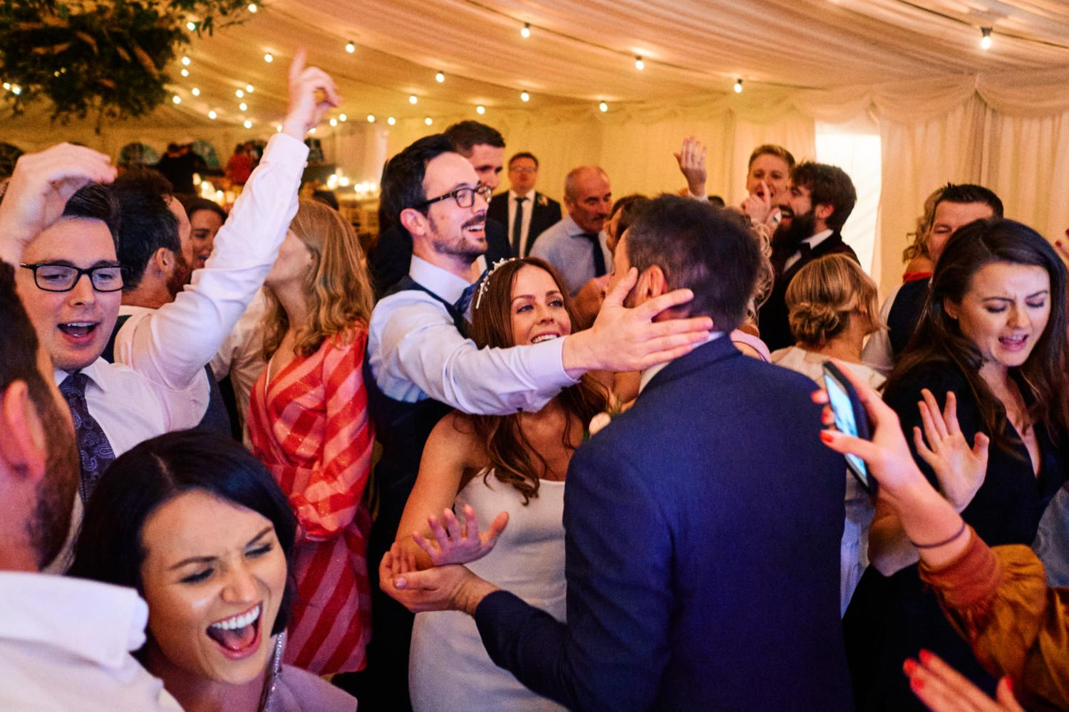 Wedding guests embrace the bride and groom at a wedding