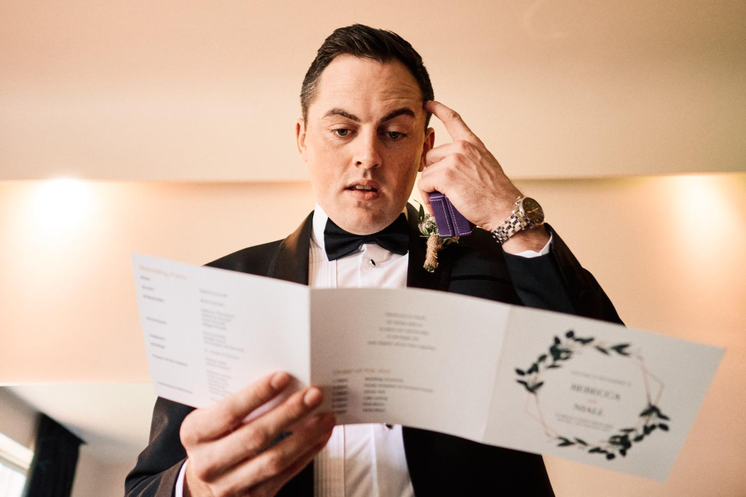 An Irish groom reads wedding service in a tuxedo