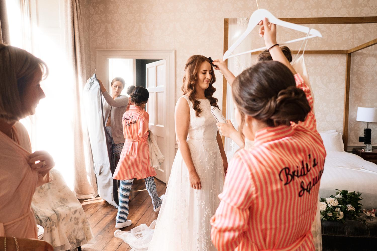 A bride tries on a wedding dress surrounded by her bridal party