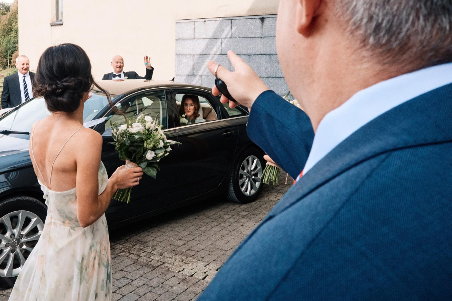 A bride and father leave for a wedding in a black car