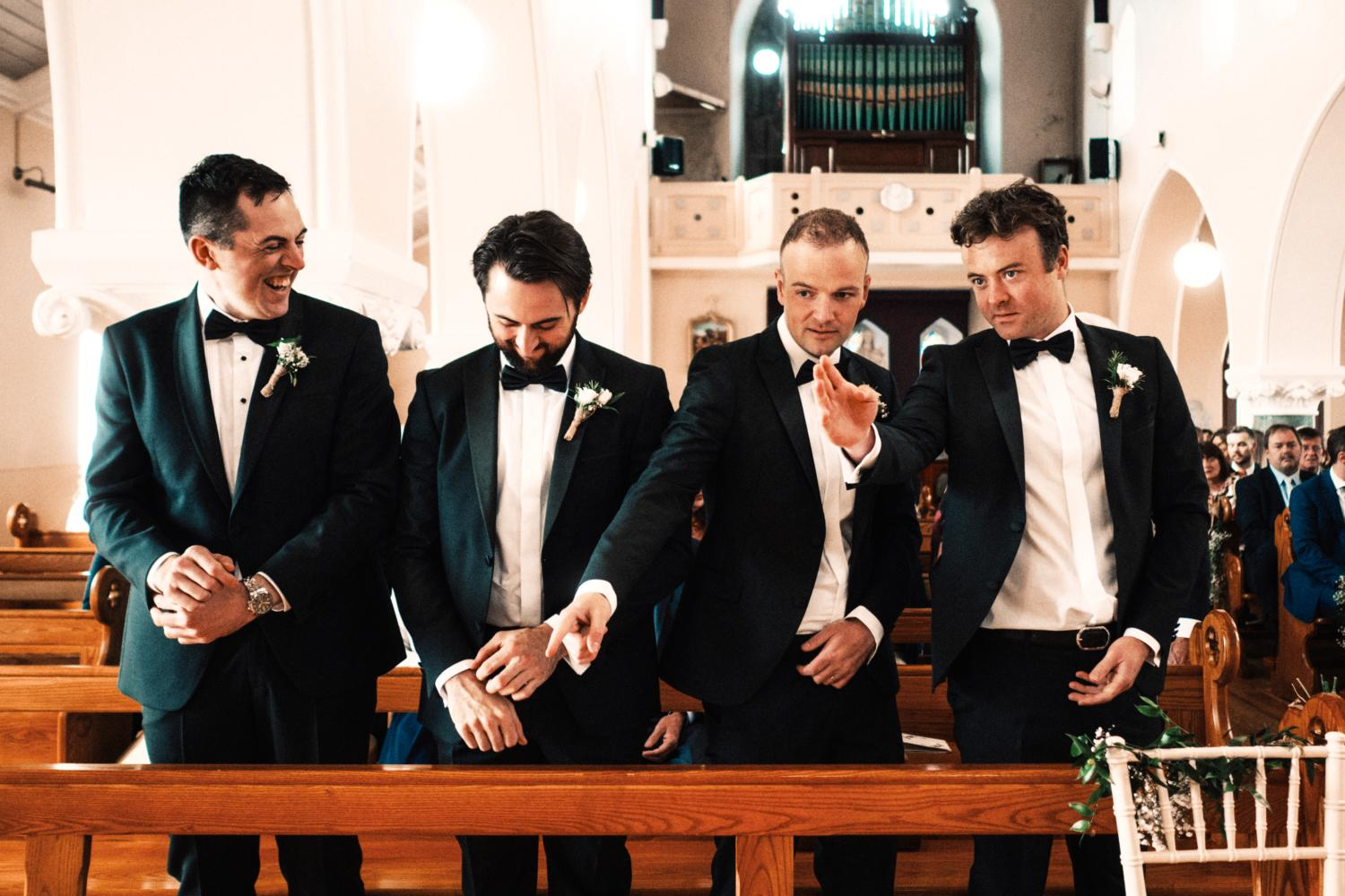 A groom and groomsmen wear tuxedos in a Catholic chapel