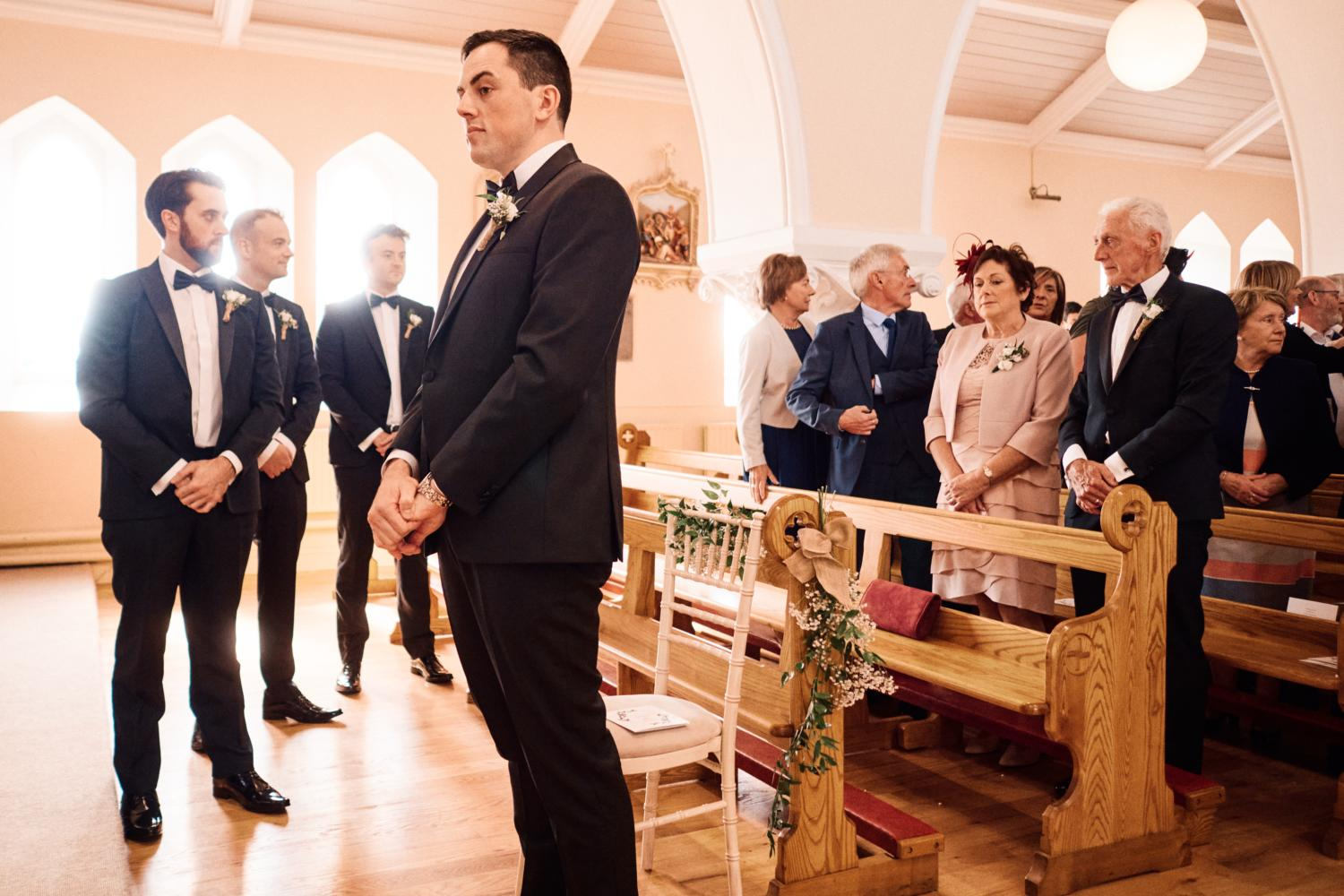 A groom in a tuxedo waits at the top of the aisle for the bride to arrive