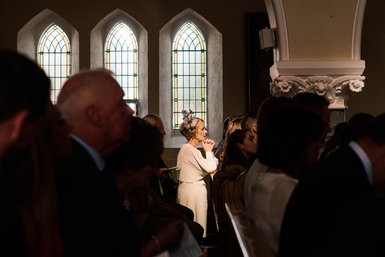 A woman prays during an Irish wedding mass