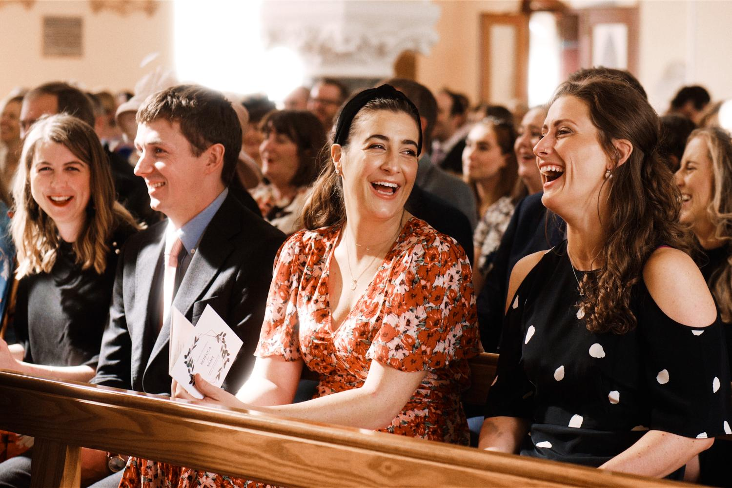 Wedding guests laugh during a wedding ceremony