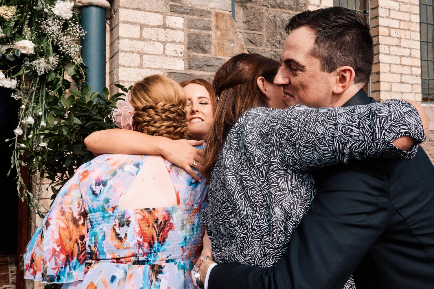 Bride and groom hug friends outside a chapel