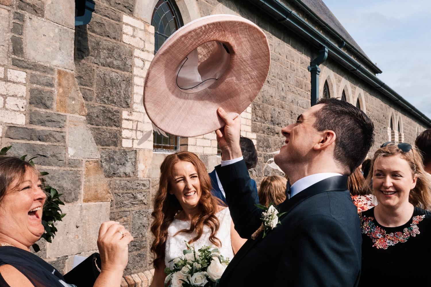 Groom lifts pink hat in the air to amusement of wedding guests