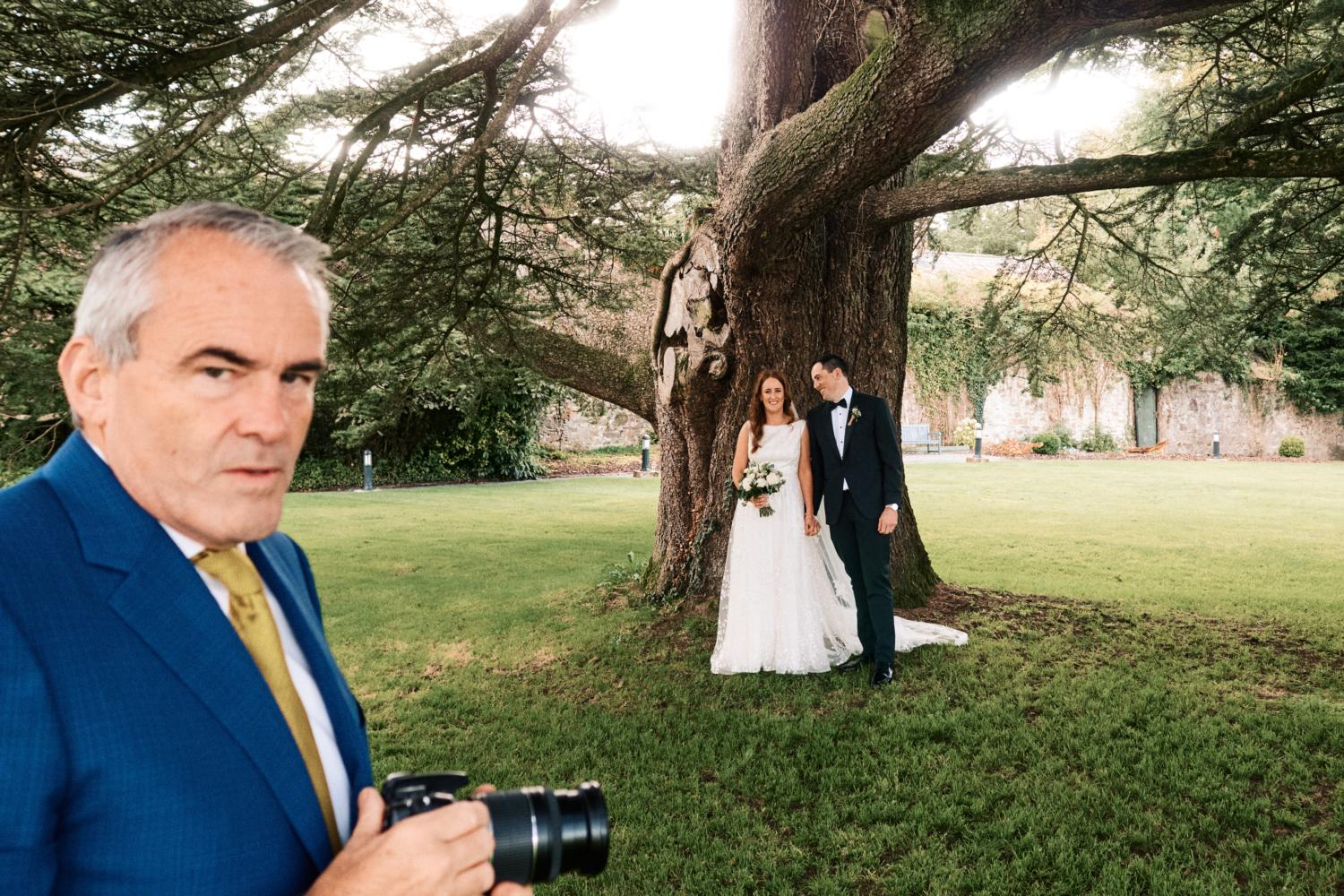A wedding guests takes photographs of the bride and groom in front of a tree