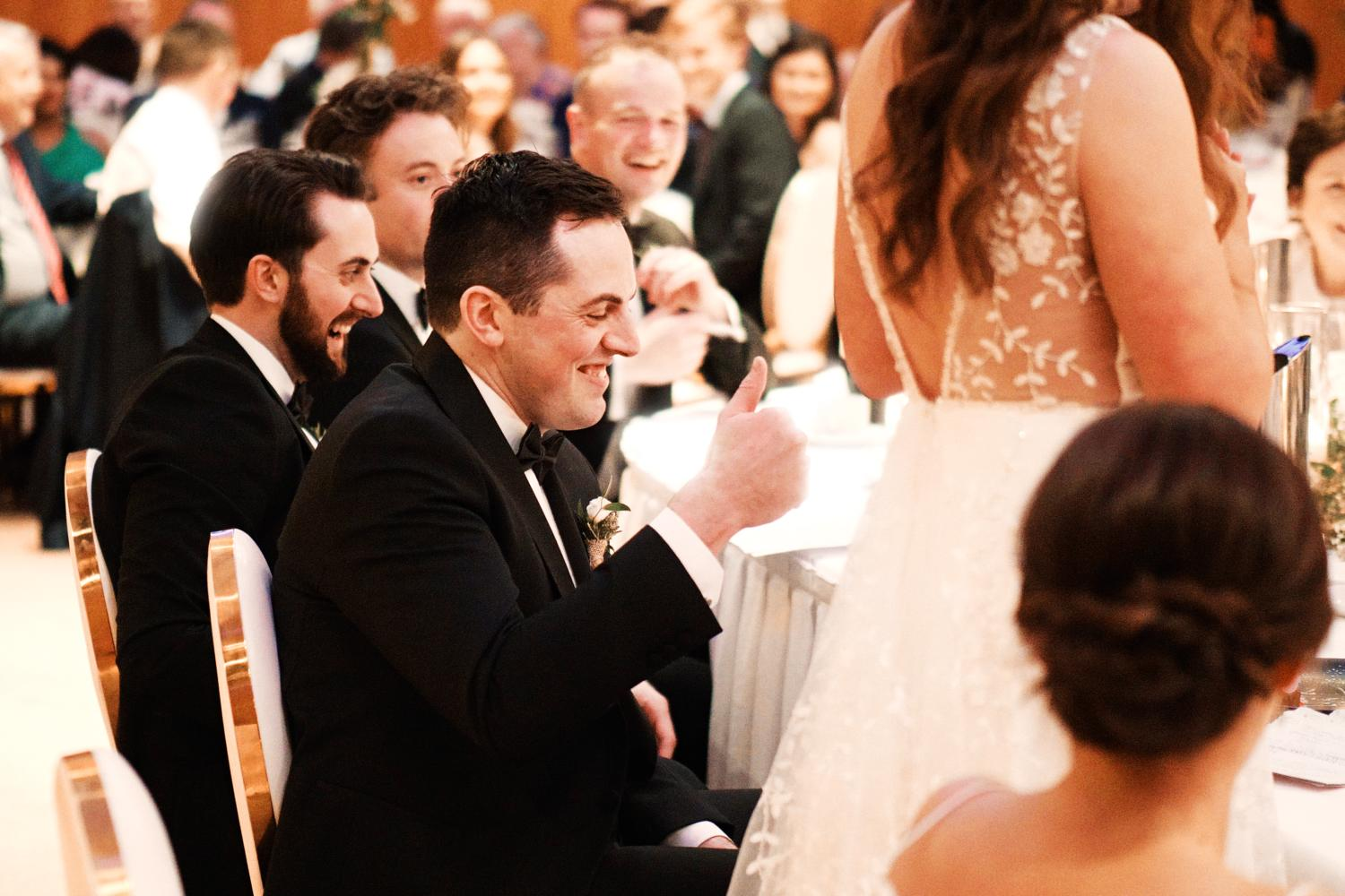 A groom raises his thumb in an approving manner during the bride's speech