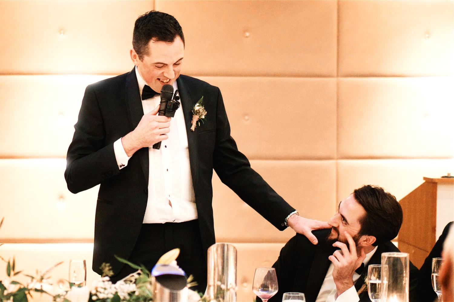 Groom affectionately touches his brother's shoulder during the speeches