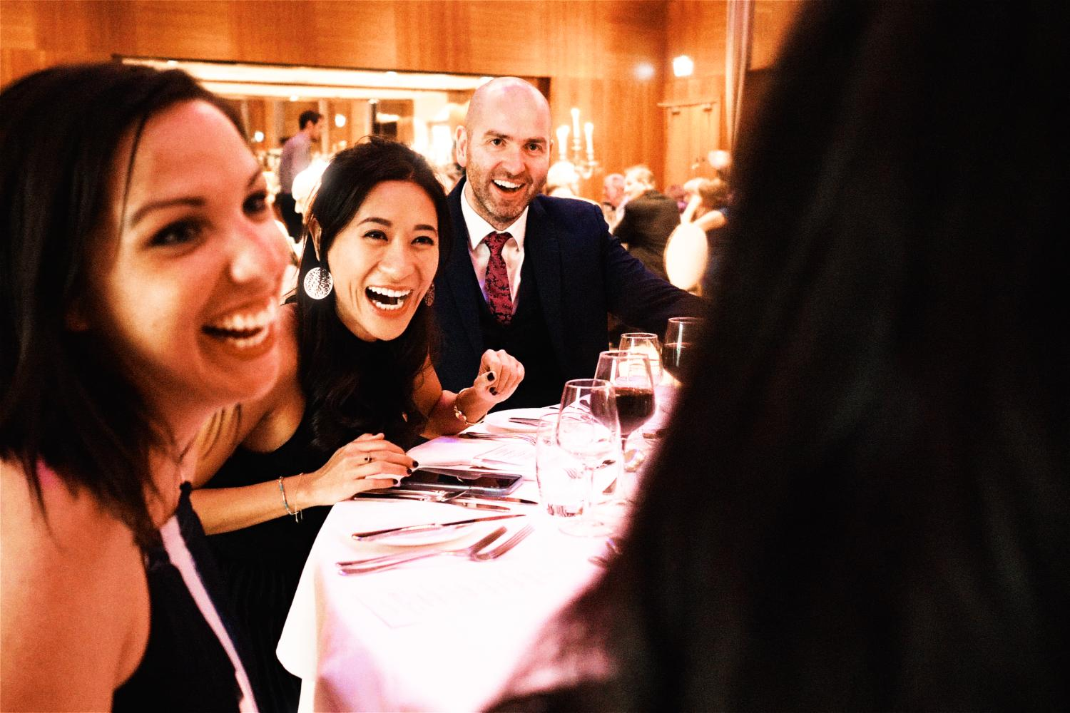 Wedding guests laugh at an evening reception