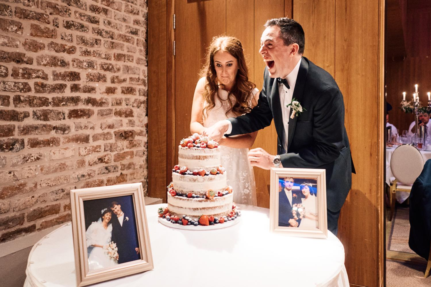 A bride and groom laugh while cutting the cake