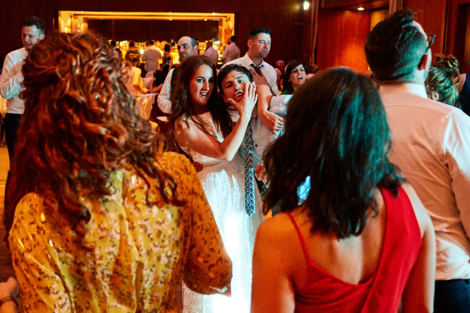 Bride squeezes friend's face on dance floor