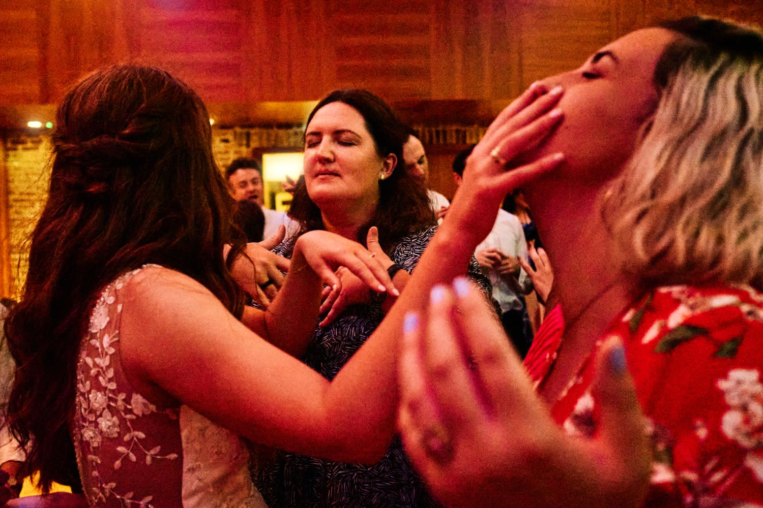 A bride touches her friend's face on a dance floor