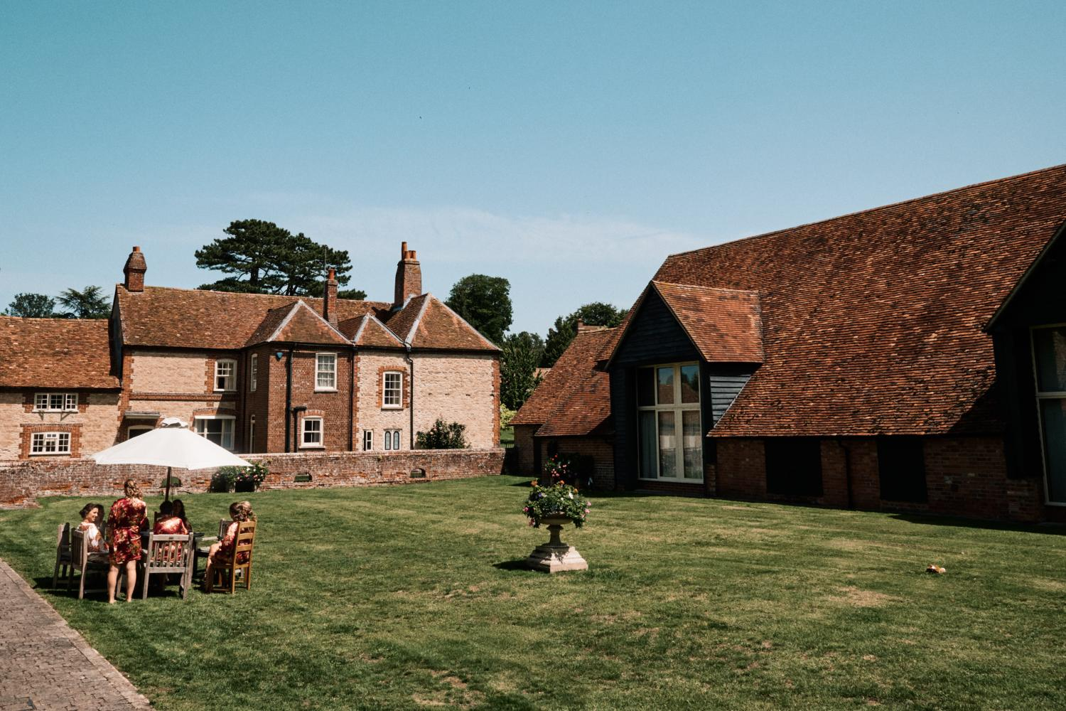 Bridal party relax outside at Ford's Farm, Ewelme