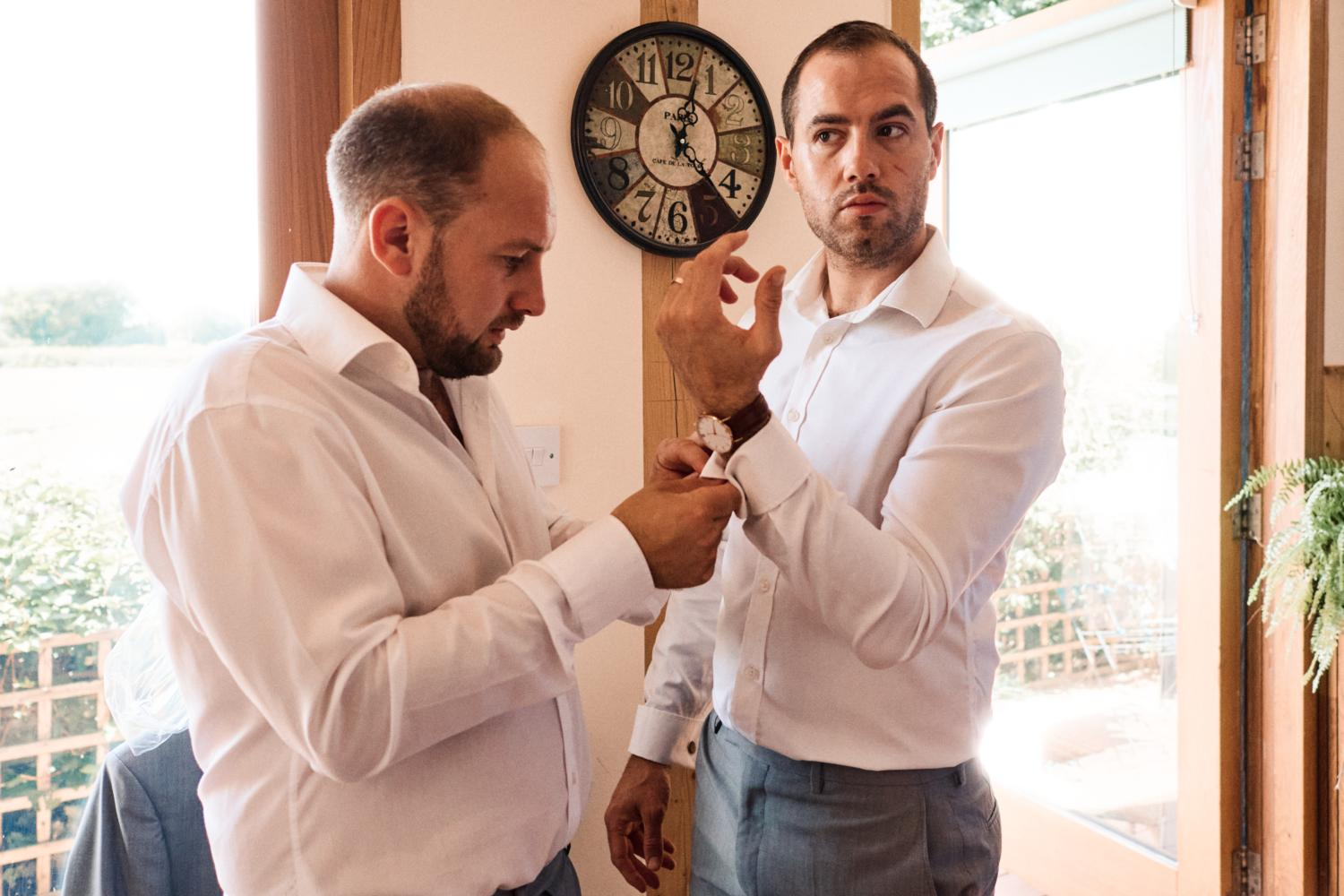 Groosmen help each with button holes at Oxfordshire wedding