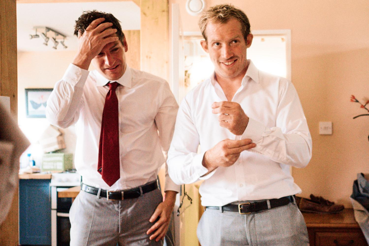 A groom fixes his cuff links with his friend