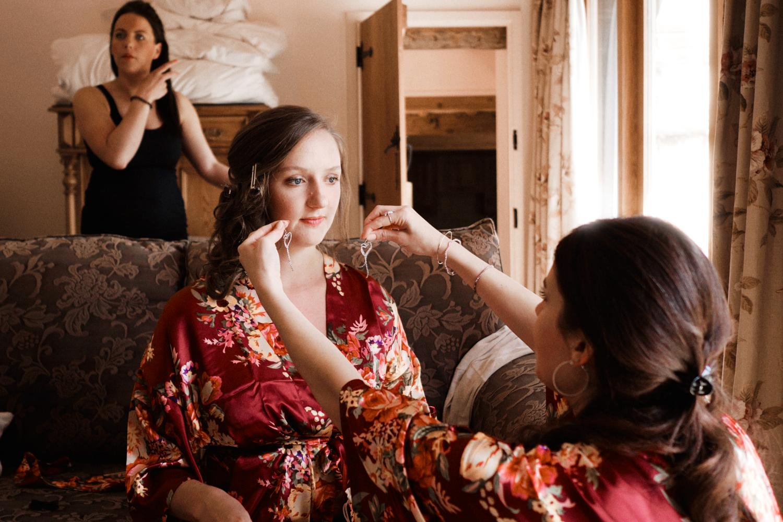 A bridesmaid helps a bridesmaid pick earrings