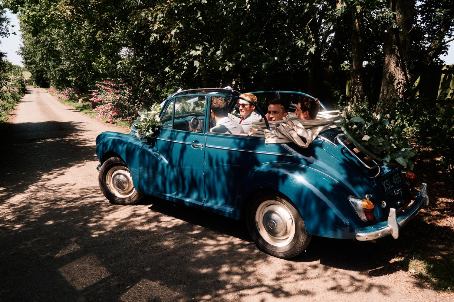 Groom and friends drive away in a blue convertible vintage car
