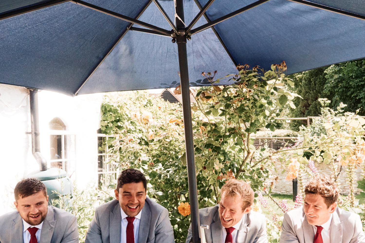 Groomsmen and three friends sit at a picnic bench